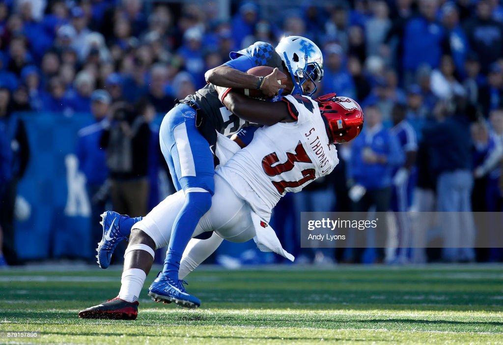 Stephen Johnson #15 of the Kentucky Wildcats is sacked by Stacy Thomas #32 of the Louisville Cardinals during the game at Commonwealth Stadium on November 25, 2017 in Lexington, Kentucky.
