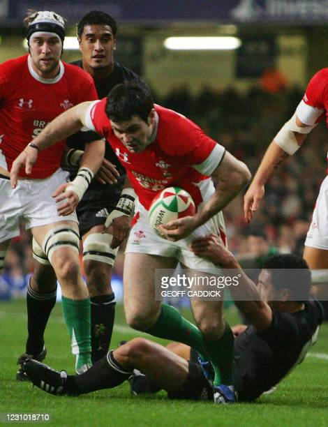 Stephen Jones of Wales fends off a tackle by Isaia Toeava of the All Blacks during the rugby union internatonal match between Wales and New Zealand...