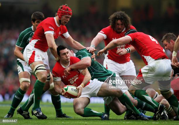 Stephen Jones of Wales looks to offload as he is brought down by John Hayes of Ireland during the RBS 6 Nations Championship match between Wales and...