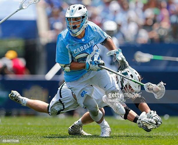 Stephen Kelly of the North Carolina Tar Heels moves the ball past Graham Savio of the Loyola Greyhounds in the first quarter during a semifinal match...