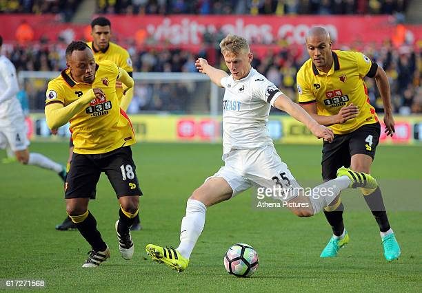 Stephen Kingsley of Swansea City crosses the ball while being marked by Juan Zuniga and Younes Kaboul of Watford during the Premier League match...