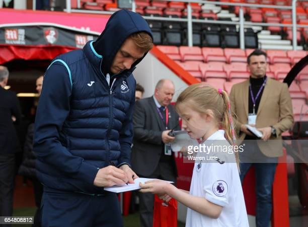 Stephen Kingsley of Swansea City signs the Swansea City mascot autograph during the Premier League match between AFC Bournemouth and Swansea City at...
