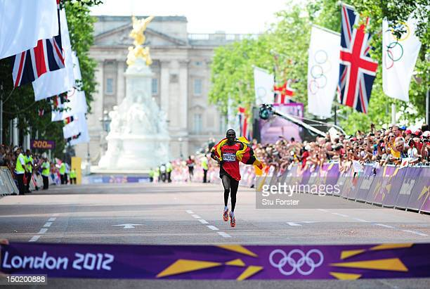 Stephen Kiprotich of Uganda backdropped by the Queen Victoria Memorial and Buckingham Palace celebrates as he approaches the line to win gold in the...