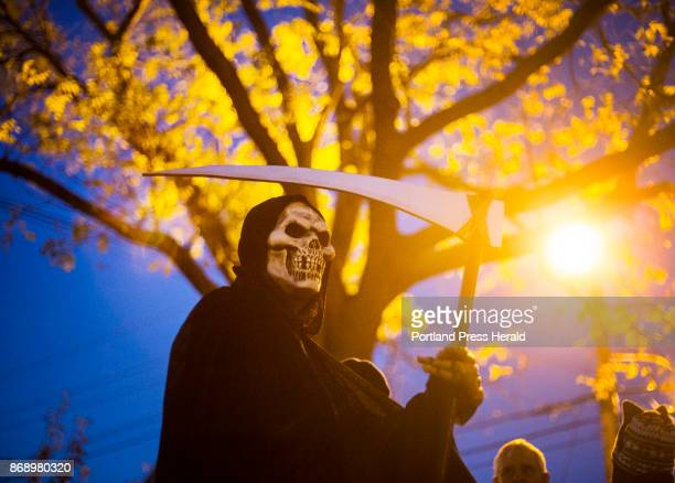 Stephen Lankford dressed as the Grim Reaper waits for the start of the annual parade on Brackett Street in Portland