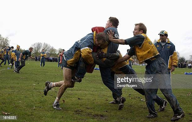 Stephen Larkham is stopped by Elton Flatly during Australian rugby union training at St Paul's School Hammersmith London England on November 12 2002