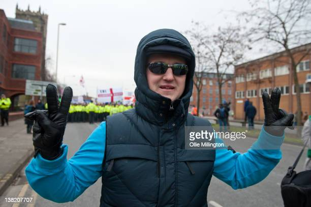Stephen Lennon AKA Tommy Robinson leader of the English Defence League poses in front of members while they march holding banners aloft during a...