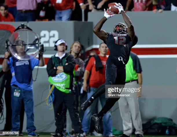Stephen Louis of the North Carolina State Wolfpack makes a leaping catch against the Louisville Cardinals during the game at Carter Finley Stadium on...