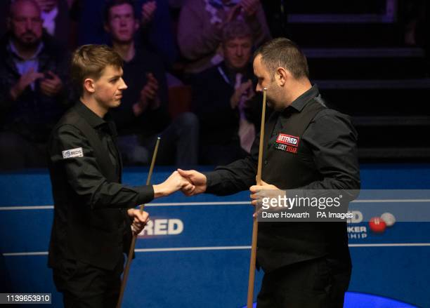 Stephen Maguire shakes hands with James Cahill after beating him during day eight of the 2019 Betfred World Championship at The Crucible Sheffield
