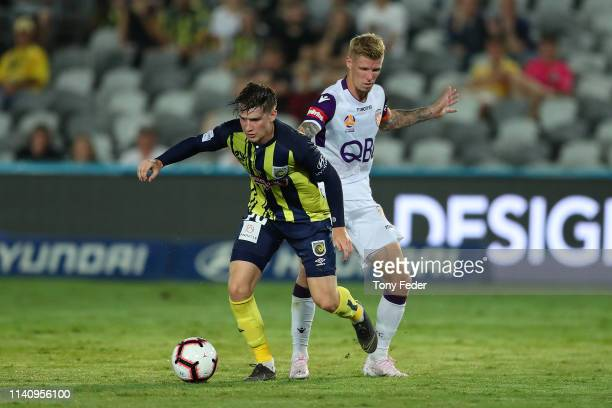 Stephen Mallon of the Central Coast Mariners contests the ball with Andy Keogh of Perth Glory during the round 24 ALeague match between the Central...