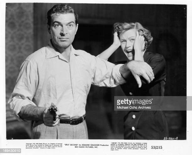 Stephen McNally holding gun as Alexis Smith screams in a scene from the film 'Split Second' 1953