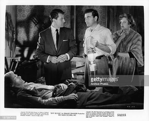 Stephen McNally holding lantern with Alexis Smith beside him in a scene from the film 'Split Second' 1953