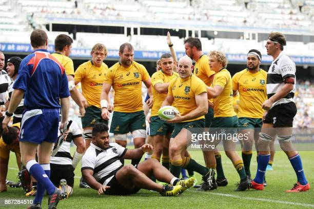 Stephen Moore of the Wallabies celebrates with team mates after scoring a try during the match between the Australian Wallabies and the Barbarians at...