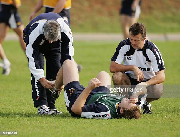 Stephen Moore the Wallaby reserve hooker receives attention to an injured ankle from Dr Martin Raftery and physio David Bick during the Wallaby...