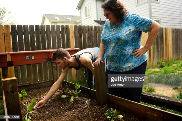 Stephen Morgan 22 and his mother Elizabeth Pate 58 checking the early plants in the backyard garden at their home in Broomfield May 07 2018...