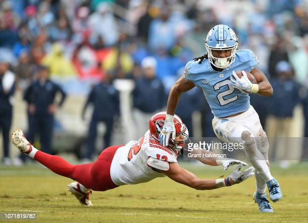 Stephen Morrison of the North Carolina State Wolfpack dives to tackle Jordon Brown of the North Carolina Tar Heels during the first half of their...