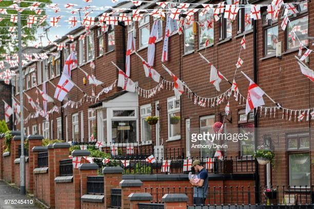 Stephen Mullane nurses his 8weekold daughter Hollie Mullane in their front garden on Wales Street in Oldham which local residents have renamed...