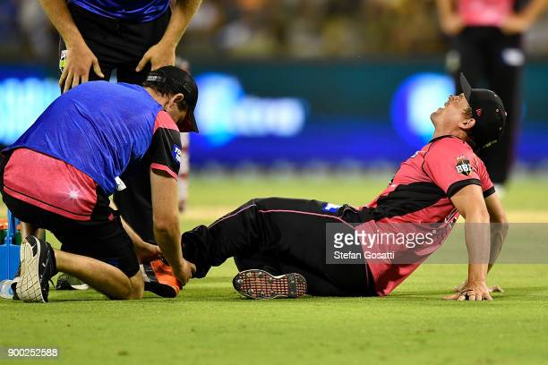 Stephen O'Keefe of the Sixers is assisted by trainers after sustaining an injury during the Big Bash League match between the Perth Scorchers and the...