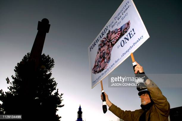 Stephen Parlato of Boulder Colorado holds up a protest sign before the campaign kickoff rally for 2020 US presidential candidate former Colorado Gov...