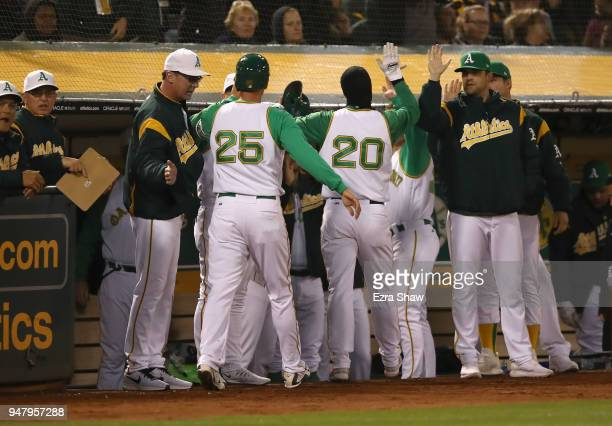 Stephen Piscotty and Mark Canha of the Oakland Athletics are congratulated by teammates after they scored on a hit by Jonathan Lucroy in the fourth...