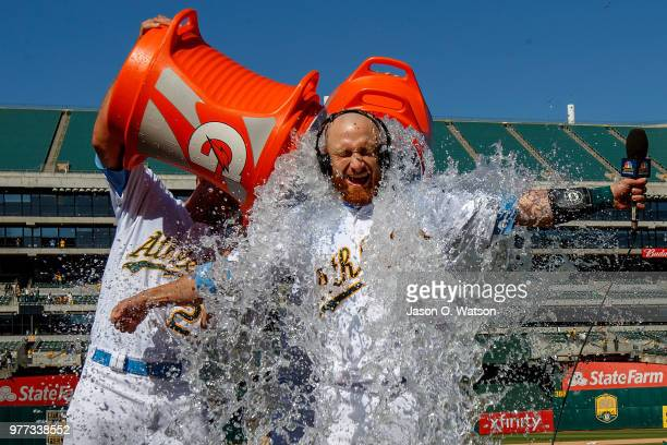Stephen Piscotty of the Oakland Athletics and Chad Pinder pour water and Gatorade on Jonathan Lucroy after he hit a walk off single against the Los...
