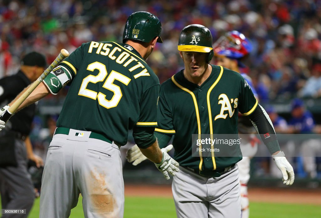 Stephen Piscotty #25 of the Oakland Athletics congratulates Mark Canha #20 for hitting a solo home run in the sixth inning against the Texas Rangers at Globe Life Park in Arlington on April 24, 2018 in Arlington, Texas.