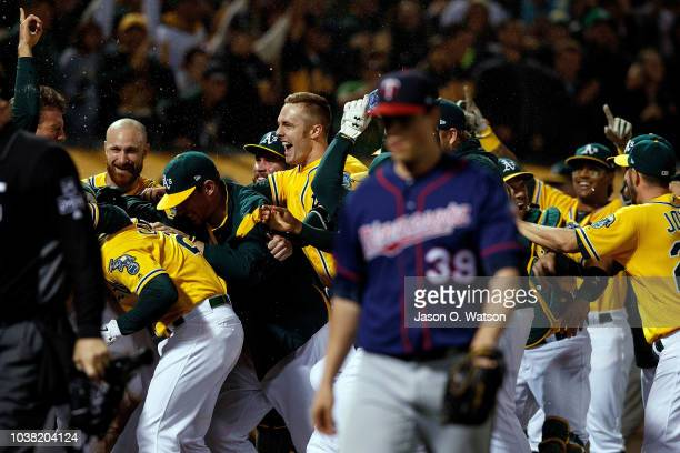 Stephen Piscotty of the Oakland Athletics is congratulated by teammates after scoring on a walk off wild pitch by Trevor Hildenberger of the...