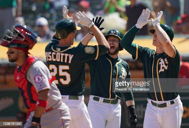 Stephen Piscotty of the Oakland Athletics is congratulated by Jed Lowrie and Matt Chapman after Piscotty hit a threerun home run against the Los...