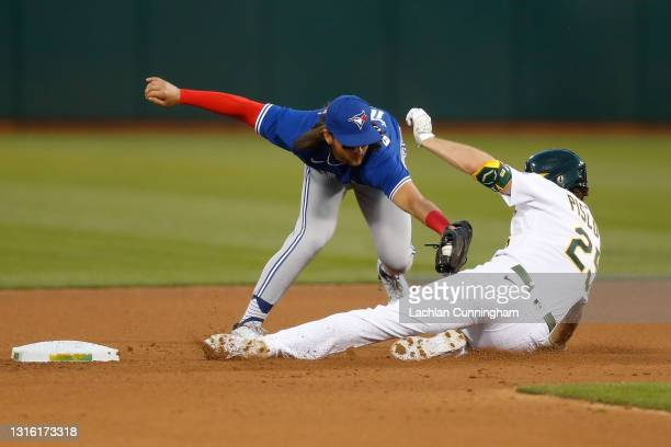 Stephen Piscotty of the Oakland Athletics is tagged out at second base by Bo Bichette of the Toronto Blue Jays in the bottom of the fourth inning at...