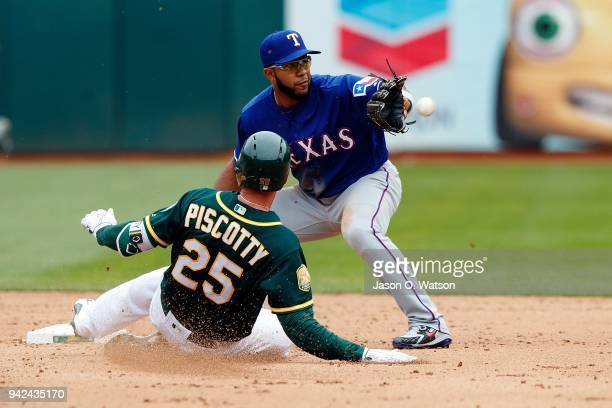 Stephen Piscotty of the Oakland Athletics is tagged out by Elvis Andrus of the Texas Rangers attempting to extend a single in the eighth inning at...
