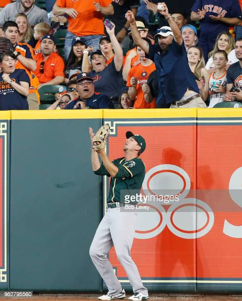 Stephen Piscotty of the Oakland Athletics leaps for a ball hit by Max Stassi of the Houston Astros in the fifth inning but is interfered with by a...