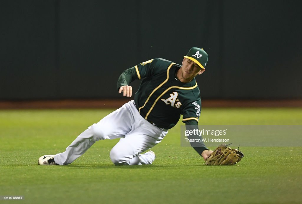 Stephen Piscotty #25 of the Oakland Athletics makes a diving catch taking a hit away from John Andreoli #57 of the Seattle Mariners in the top of the seventh inning at the Oakland Alameda Coliseum on May 23, 2018 in Oakland, California.