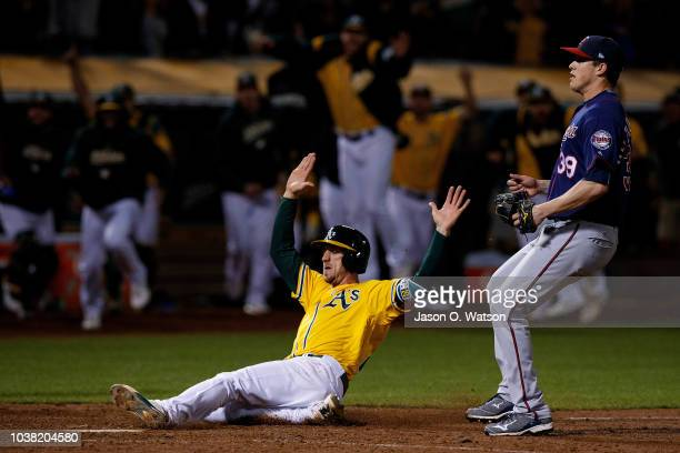 Stephen Piscotty of the Oakland Athletics slides into home plate to score on a walk off wild pitch by Trevor Hildenberger of the Minnesota Twins...