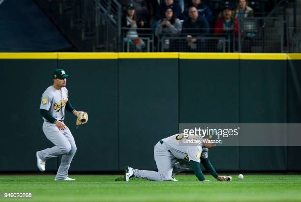 Stephen Piscotty of the Oakland Athletics stumbles as he tries to retrieve the double by Dee Gordon of the Seattle Mariners as Jake Smolinski runs...