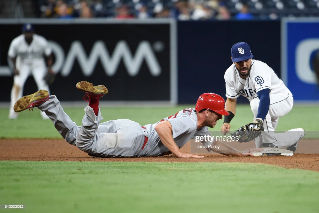 Stephen Piscotty #55 of the St. Louis Cardinals gets back to second base ahead of the tag of Carlos Asuaje #20 of the San Diego Padres during the ninth inning of a baseball game at PETCO Park on September 6, 2017 in San Diego, California.