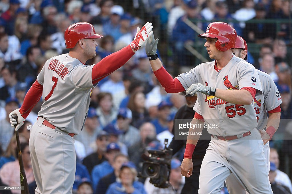 Stephen Piscotty #55 of the St. Louis Cardinals high fives Matt Holliday #7 of the St. Louis Cardinals after hitting a two-run home run in the first inning against the Chicago Cubs during game four of the National League Division Series at Wrigley Field on October 13, 2015 in Chicago, Illinois.