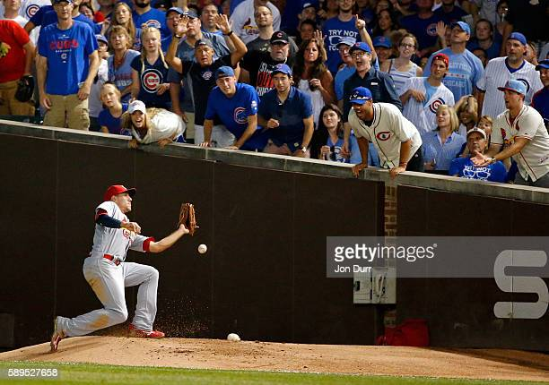 Stephen Piscotty of the St Louis Cardinals is unable to make a catch against the Chicago Cubs in foul territory during the fourth inning at Wrigley...