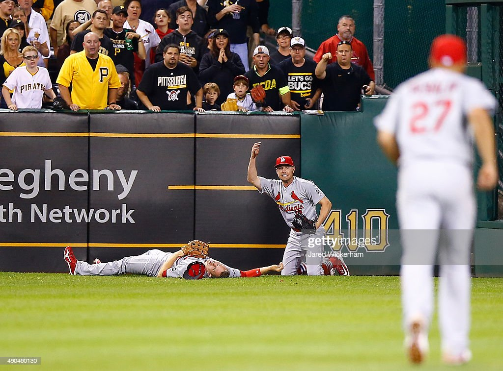 Stephen Piscotty #55 of the St Louis Cardinals lays on the ground while teammate Peter Bourjos #8 calls for the medical staff after colliding on a sliding catch from a ball hit by Josh Harrison #5 of the Pittsburgh Pirates in the 7th inning during the game at PNC Park on September 28, 2015 in Pittsburgh, Pennsylvania. Piscotty would be carted off of the field on a stretcher.