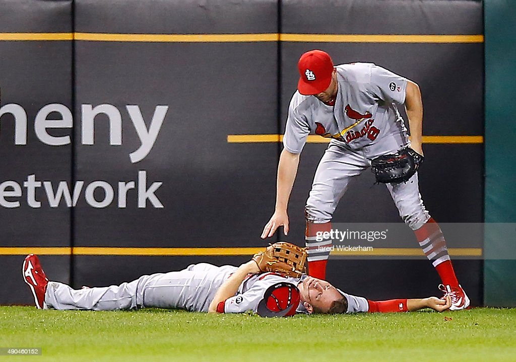 Stephen Piscotty #55 of the St Louis Cardinals lays on the ground while teammate Peter Bourjos #8 waits for the medical staff after colliding on a sliding catch from a ball hit by Josh Harrison #5 of the Pittsburgh Pirates in the 7th inning during the game at PNC Park on September 28, 2015 in Pittsburgh, Pennsylvania. Piscotty would be carted off of the field on a stretcher.