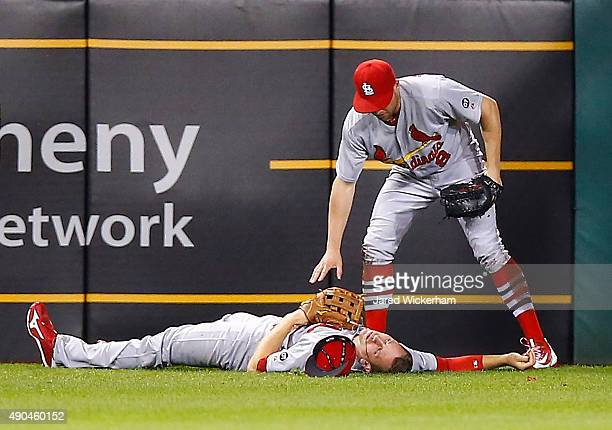Stephen Piscotty of the St Louis Cardinals lays on the ground while teammate Peter Bourjos waits for the medical staff after colliding on a sliding...