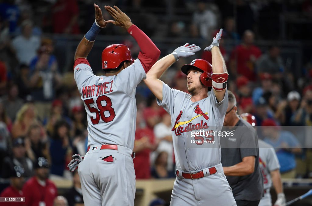 Stephen Piscotty #55 of the St. Louis Cardinals, right, is congratulated by Jose Martinez #58 after hitting a two-run home run during the seventh inning of a baseball game against the San Diego Padres at PETCO Park on September 6, 2017 in San Diego, California.