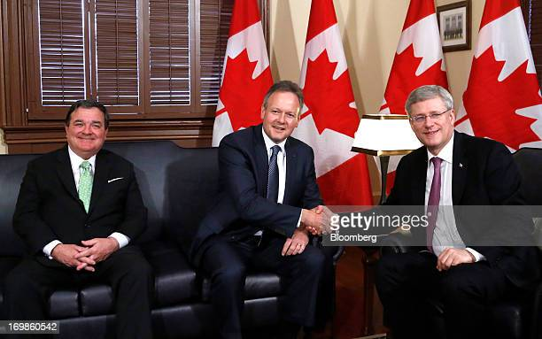 Stephen Poloz, governor of the Bank of Canada, center, shakes hands with by Stephen Harper, Canada's prime minister, right, while being welcomed into...