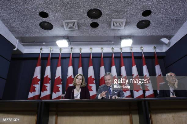 Stephen Poloz governor of the Bank of Canada center speaks while Carolyn Wilkins senior deputy governor at the Bank of Canada listens during a news...