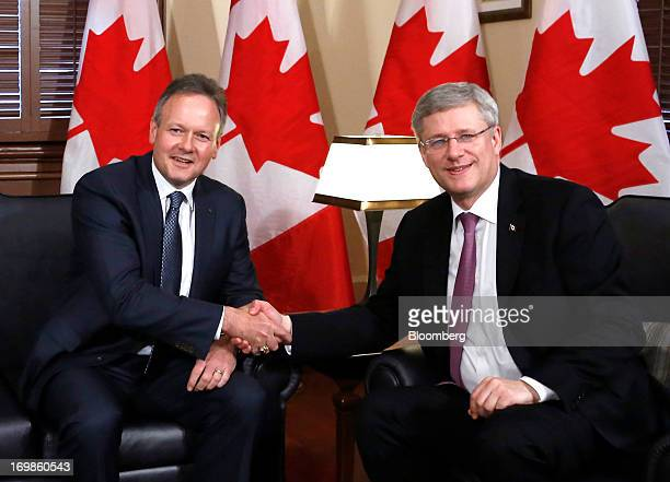 Stephen Poloz, governor of the Bank of Canada, left, shakes hands with by Stephen Harper, Canada's prime minister, right, while being welcomed into...