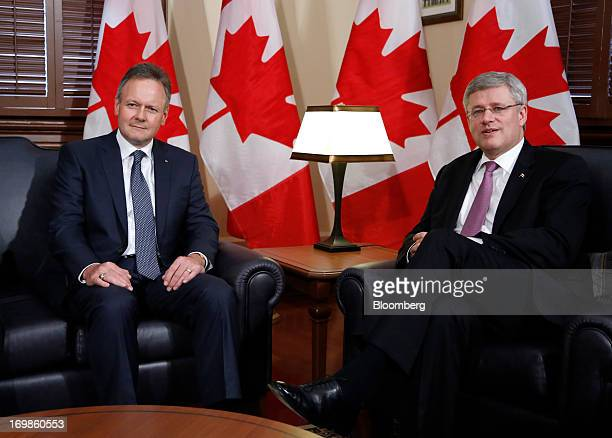 Stephen Poloz, governor of the Bank of Canada, left, sits for a photograph with Stephen Harper, Canada's prime minister, while being welcomed into...