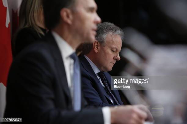 Stephen Poloz governor of the Bank of Canada right listens while Bill Morneau Canada's minister of finance speaks during a news conference in Ottawa...