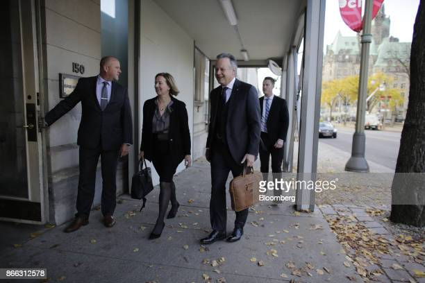 Stephen Poloz governor of the Bank of Canada second right and Carolyn Wilkins senior deputy governor at the Bank of Canada second left arrive for a...