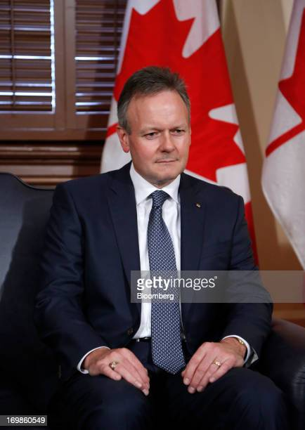 Stephen Poloz, governor of the Bank of Canada sits for photographers while being welcomed into office by Stephen Harper, Canada's prime minister, not...