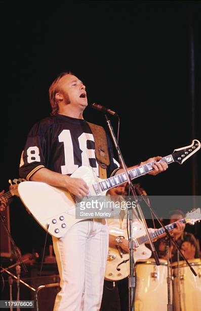 Stephen Stills US guitarist playing a guitar while singing into a microphone circa 1975