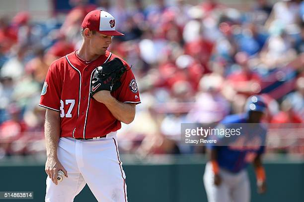 Stephen Strasburg of the Washington Nationals checks a runner at first during a spring training game against the New York Mets at Space Coast Stadium...