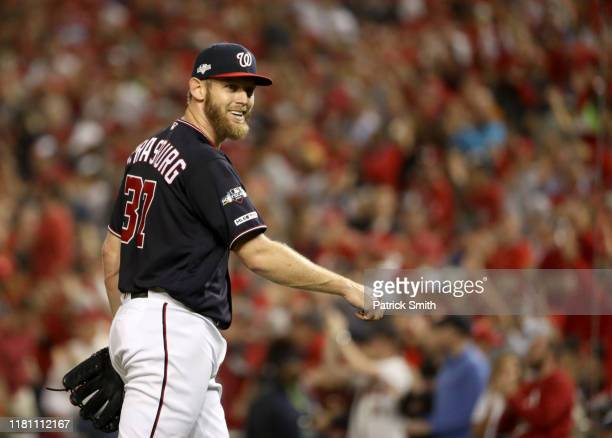 Stephen Strasburg of the Washington Nationals smiles as he walks back to the dug out in the fifth inning of game three of the National League...